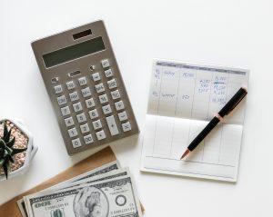 Calculatrice et livre de comptes entreprise sur une table avec des billets